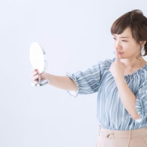 鏡を見て鼻を指す女性