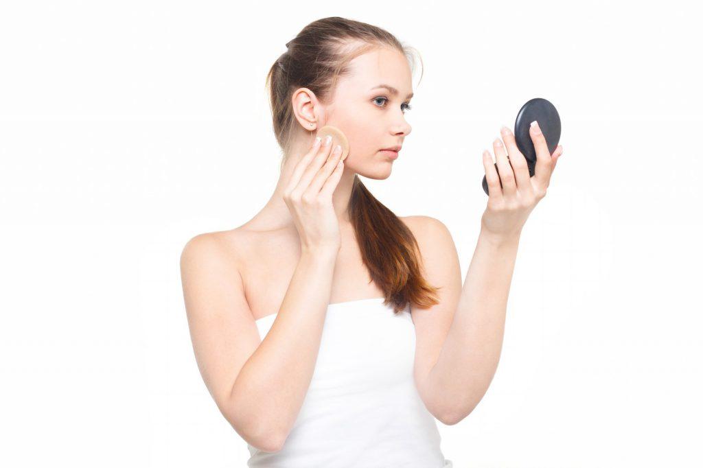化粧でにきびを隠そうとする女性